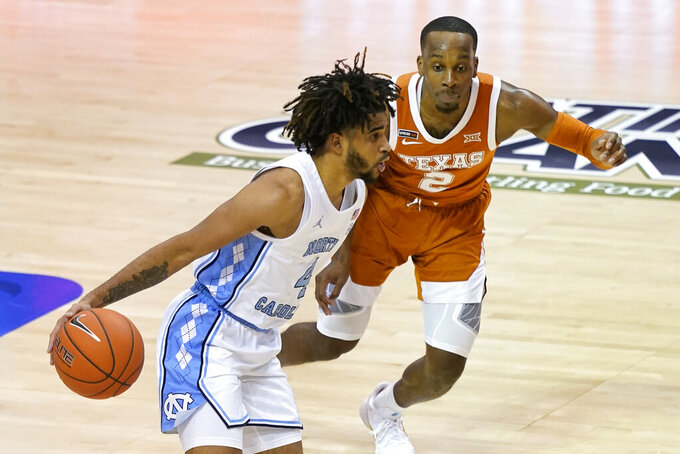 North Carolina guard R.J. Davis (4) drives the ball past Texas guard Matt Coleman III (2) in the second half of an NCAA college basketball game for the championship of the Maui Invitational, Wednesday, Dec. 2, 2020, in Asheville, N.C. Texas won 69-67. (AP Photo/Kathy Kmonicek)