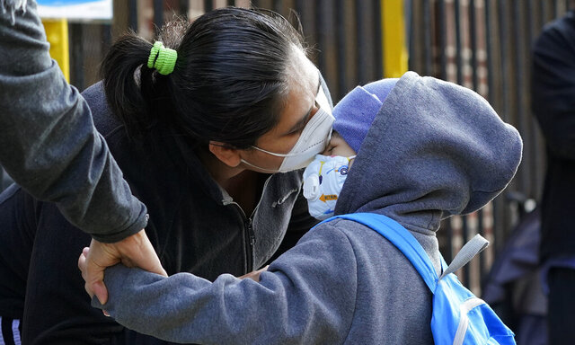 Maria Flores kisses her son Pedro Garcia, 4, while a teacher takes his hand as he arrives for the first day of school at the Mosaic Pre-K Center in Queens, Monday, Sept. 21, 2020, in New York. The city public schools delayed reopening for two weeks. (AP Photo/Mark Lennihan)