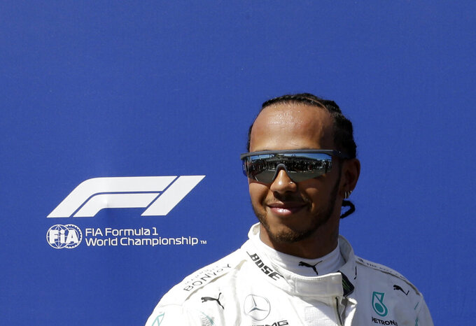 Mercedes driver Lewis Hamilton of Britain smiles after he clocked the fastest time during the qualifying session at the Paul Ricard racetrack in Le Castellet, southern France, Saturday, June 22, 2019. The French Formula One Grand Prix will be held on Sunday. (AP Photo/Claude Paris)