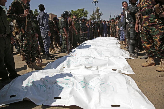 Police troopers stand around bags containing the bodies of nine men, convicted of involvement in the killing of a senior Houthi official Saleh al-Samad after their execution at Tahrir Square in Sanaa, Yemen Saturday, Sept. 18, 2021. Yemen's Houthi rebels on Saturday said they executed nine people for their alleged involvement in the killing of a senior Houthi official in an airstrike by the Saudi-led coalition more than three years ago. (AP Photo/Hani Mohammed)