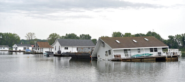 A partially-submerged houseboat is shown, Aug. 4, 2020, at Horseshoe Pond at Presque Isle State Park near Erie, Pa. About half of the houseboat was initially submerged. There were no injuries, authorities reported. Crews from Erie-based Lakeshore Towing Services Inc. worked throughout the week to raise the houseboat to a nearly level position. (Christopher Millette/Erie Times-News via AP)
