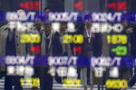 Pedestrian are reflected on an electronic stock board showing Japan's Nikkei 225 index at a securities firm in Tokyo Friday, Dec. 13, 2019. Shares likewise jumped Friday in Asia following fresh all-time highs overnight on Wall Street spurred by optimism that the U.S. and China are close to reaching a deal to end their costly trade war. (AP Photo/Eugene Hoshiko)