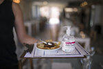 A waitress carries menus and hand sanitizer at a seafood restaurant in Marseille, southern France, Tuesday, June 2, 2020. The French way of life resumes Tuesday with most virus-related restrictions easing as the country prepares for the summer holiday season amid the pandemic. (AP Photo/Daniel Cole)