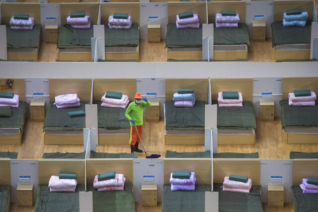 In this photo released by Xinhua News Agency, a worker cleans the floor of a temporary hospital with 1,100 beds converted from the Wuhan Sports Center in Wuhan in central China's Hubei Province, Wednesday, Feb. 12, 2020. Without enough facilities to handle the number of cases of viral infection, Wuhan has been building prefabricated hospitals and converting a gym and other large spaces to house patients and try to isolate them from others. (Xiao Yijiu/Xinhua via AP)