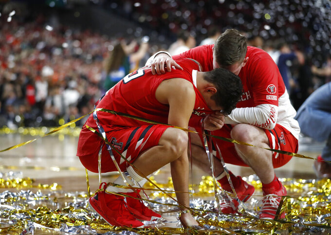 Texas Tech guard Davide Moretti, left, reacts with a teammate at the end of the championship game against Virginia in the Final Four NCAA college basketball tournament, Monday, April 8, 2019, in Minneapolis. Virginia won 85-77 in overtime. (AP Photo/Jeff Roberson)