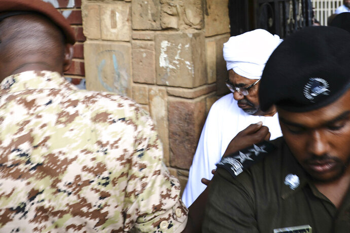 Sudan's ousted president Omar al-Bashir is escorted into a vehicle as he returns to prison following his appearance before prosecutors over charges of corruption and illegal possession of foreign currency, in Khartoum the capital of Sudan on Sunday June 16, 2019. The deposed strongman has been held under arrest in the capital since the military removed him from power in April amid mass public protests against his 30-year rule.(AP Photo/Mahmoud Hjaj)