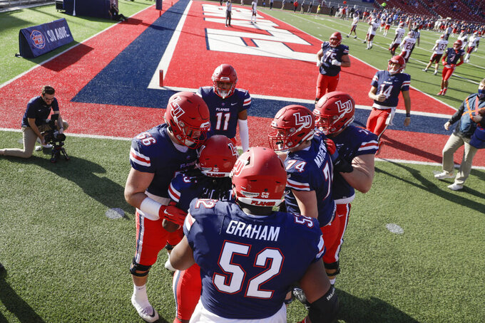 Liberty players celebrate a Peytton Pickett (25) touchdown during the second half of a NCAA college football game against Massachusetts on Friday, Nov. 27, 2020, at Williams Stadium in Lynchburg, Va. (AP Photo/Shaban Athuman)