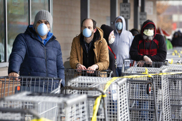 People wait to enter a supermarket that is limiting the number of customers at any one time, Friday, April 3, 2020, in Chelsea, Mass. The new coronavirus causes mild or moderate symptoms for most people, but for some, especially older adults and people with existing health problems, it can cause more severe illness or death. (AP Photo/Michael Dwyer)