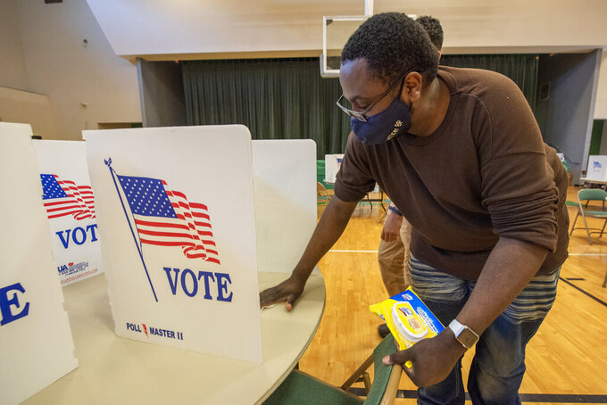 Precinct 51 poll worker Brian Pippins, of Jackson, Miss., wipes tables with disinfectant helping to keep voting safe during the pandemic as voters head to the polls in Jackson, Miss., for citywide primary elections, Tuesday, April 6, 2021. Winners for Jackson mayor and city council will advance to either runoffs or the city's June 8 general election. (Barbara Gaunt/The Clarion-Ledger via AP)