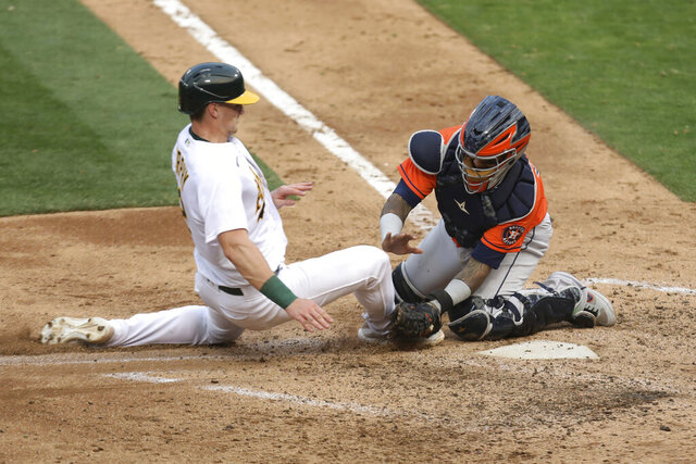 Oakland Athletics' Sean Murphy is tagged out at home by Houston Astros' Martin Maldonado during the seventh inning of the first baseball game of a doubleheader in Oakland, Calif., Tuesday, Sept. 8, 2020. (AP Photo/Jed Jacobsohn)