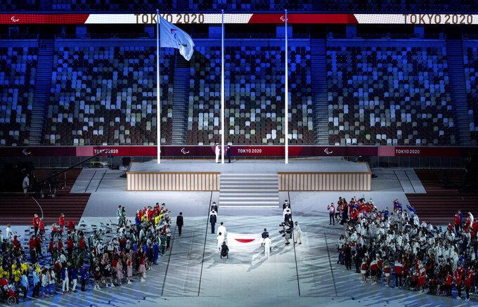 The national flag of Japan is handed over to members of the Japan Self-Defense Forces by flag bearers Motoki Iwakiri (Athletics), Tomoki Sato (Athletics), Miyuki Yamada (Swimming), Sakura Koike (Swimming), Kazuyasu Minobe (Fencing) and Keiko Yamamoto (Nurse) during the closing ceremony of the Tokyo 2020 Paralympic Games in Tokyo, Japan, Sunday, Sept. 5, 2021. (Joe Toth for OIS via AP)