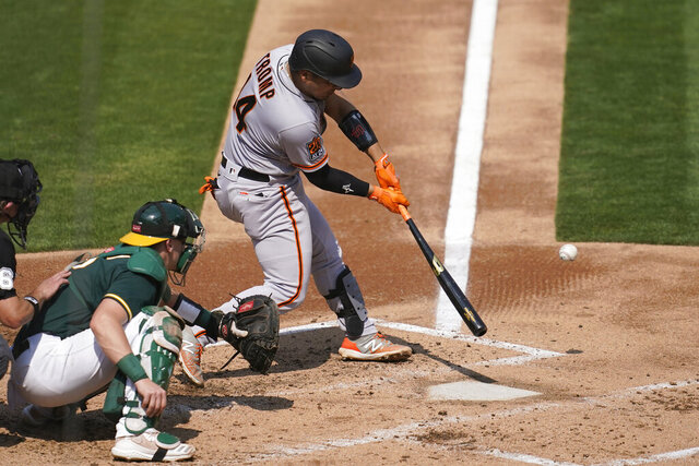 San Francisco Giants' Chadwick Tromp, right, hits a two-run home run in front of Oakland Athletics catcher Sean Murphy during the third inning of a baseball game in Oakland, Calif., Sunday, Sept. 20, 2020. (AP Photo/Jeff Chiu)