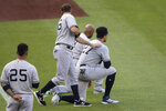 New York Yankees' Gleyber Torres (25) stands as DJ LeMahieu (26) touches Aaron Hicks (31) and Giancarlo Stanton (27) as they kneel during the playing of the national anthem before a baseball game against the Washington Nationals at Nationals Park, Saturday, July 25, 2020, in Washington. (AP Photo/Alex Brandon)
