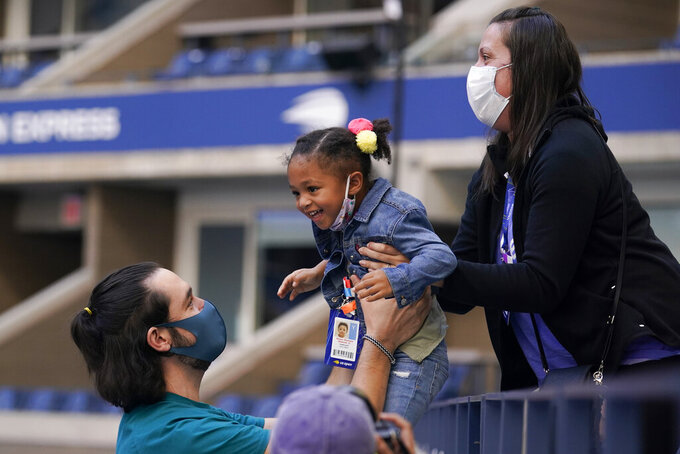 Three-year-old Alexis Olympia Ohanian Jr., center, daughter of Serena Williams, of the United States, is handed down to courtside after watching her mother play against Sloane Stephens, of the United States, during the third round of the US Open tennis championships, Saturday, Sept. 5, 2020, in New York. (AP Photo/Seth Wenig)