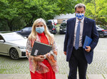 Melanie Huml, Health Minister of the German state of Bavaria, left, and Bavaria's governor Markus Soeder, right, arrive for a joint press conference in Munich, Germany, Thursday, Aug. 13, 2020. (Peter Kneffel/dpa via AP)