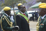 Zimbabwean President Emmerson Mnangagwa inspects the guard of honour during the opening session of parliament in Harare, Tuesday, Oct, 1, 2019. Zimbabwe's opposition lawmakers have walked out of Parliament as President Emmerson Mnangagwa presented his state of the nation address, a sign of the political tensions still gripping the country. (AP Photo/Tsvangirayi Mukwazhi)