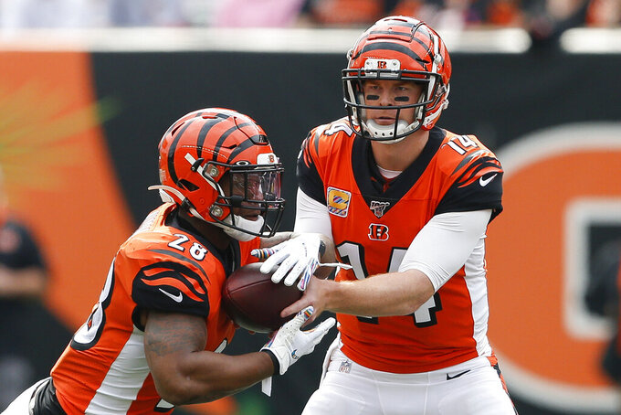 Cincinnati Bengals quarterback Andy Dalton (14) hands the ball to running back Joe Mixon (28) in the first half of an NFL football game against the Arizona Cardinals, Sunday, Oct. 6, 2019, in Cincinnati. (AP Photo/Gary Landers)