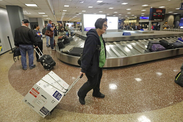 In this Jan. 31, 2020, photo, Ann Lovell carries her box of prescriptions after returning to Salt Lake City International Airport following her visit to Tijuana, Mexico. Lovell travels every few months to Tijuana, Mexico, to buy medication for rheumatoid arthritis with tickets paid for by the state of Utah's public insurer. Lovell is one of about 10 state workers participating in a year-old program to lower prescription drug costs by having public employees buy their medication in Mexico at a steep discount compared to U.S. prices. (AP Photo/Rick Bowmer)