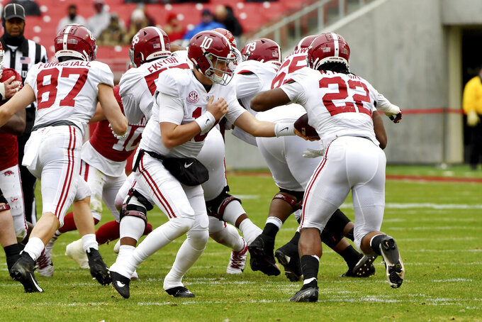 Alabama quarterback Mac Jones (10) hands off the ball to running back Najee Harris against Arkansas during the first half of an NCAA college football game Saturday, Dec. 12, 2020, in Fayetteville, Ark. (AP Photo/Michael Woods)