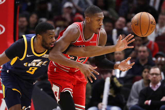Utah Jazz guard Emmanuel Mudiay, left, and Chicago Bulls guard Kris Dunn battle for the ball during the first half of an NBA basketball game in Chicago, Thursday, Jan. 2, 2020. (AP Photo/Nam Y. Huh)
