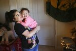 Seanna Leilani Chavez, left, holds Athena Chavez, 2, the sister and daughter of Aaron Francisco Chavez respectively, as the two stand next to a shrine for Aaron at the family home Wednesday, Feb. 6, 2019, in Tucson, Ariz. Aaron Chavez died of a fentanyl overdose at the age of 19. (AP Photo/Ross D. Franklin)