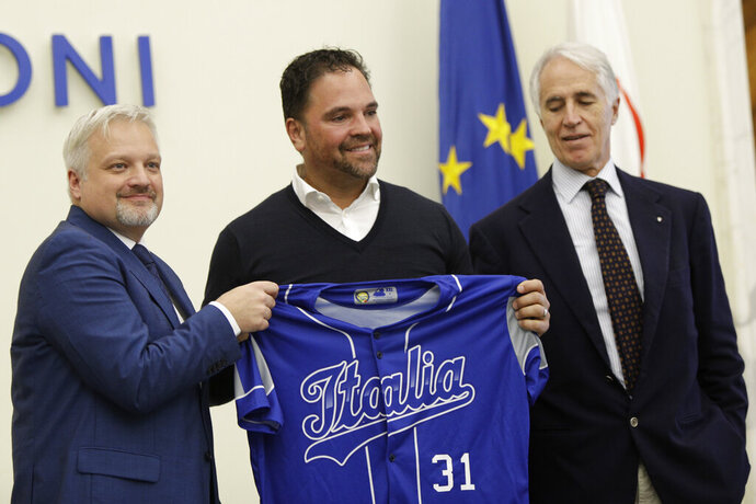 Hall of Fame catcher Mike Piazza shows his jersey during his presentation as Italy's national baseball team coach, at the Italian Olympic Committee headquarters in Rome, Friday, Nov. 29, 2019. At right is Olympic Committee president Giovanni Malago' and at left is the President of the Italian Baseball Federation Andrea Marcon. (AP Photo/Alberto Pellaschiar)