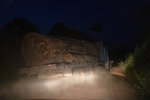 In this Nov. 28, 2019 photo, a logging truck without license plates carries the trunk of a giant tree on a dirt road away from Trairao National Forest in Trairao, Para state, Brazil. Night after night, truckers chug along the darkened road to their turn-off into the woods, where they deliver their ancient cargo. By morning, the logs are laid out for hewing at the remote sawmill, its corrugated metal roof hardly visible from the highway.(AP Photo/Leo Correa)