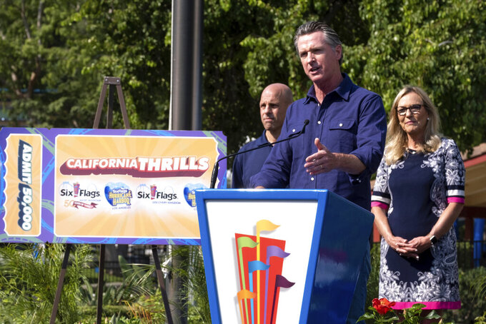 California Gov. Gavin Newsom welcomes the public to Six Flags Magic Mountain in Santa Clarita, Calif. Wednesday, June 16, 2021. At left, is Michael Spanos, President of Six Flags, at right is LA county supervisor Kathryn Barger. Newsom continued his tour of the state after lifting most COVID-19 restrictions Tuesday. (David Crane/The Orange County Register via AP)