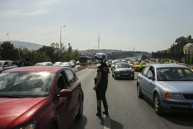 Police inspect passengers in vehicles on the July 15 Martyrs' Bridge, formerly known as the Bosphorus Bridge in Istanbul, Friday, April 30, 2021, on the first day of a tight lockdown to help protect from the spread of the coronavirus. Turkish security forces on Friday patrolled main streets and set up checkpoints at entry and exits points of cities, to enforce Turkey's strictest COVID-19 lockdown to date. Still, many people were on the move as the government, desperate not to shut down the economy completely, kept some sectors exempt from the restrictions. (AP Photo/Emrah Gurel)