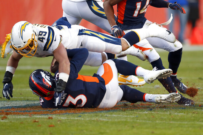 Denver Broncos quarterback Drew Lock is tackled by Los Angeles Chargers linebacker Drue Tranquill during the first half of an NFL football game Sunday, Dec. 1, 2019, in Denver. (AP Photo/David Zalubowski)