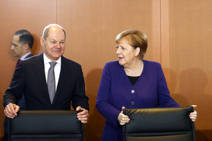 German Chancellor Angela Merkel, right, arrives with Vice Chancellor and Finance Minister Olaf Scholz, left, for the weekly cabinet meeting of the German government at the chancellery in Berlin, Germany, Wednesday, Dec. 11, 2019. In the back ground left German Foreign Minister Heiko Maas. (AP Photo/Markus Schreiber)