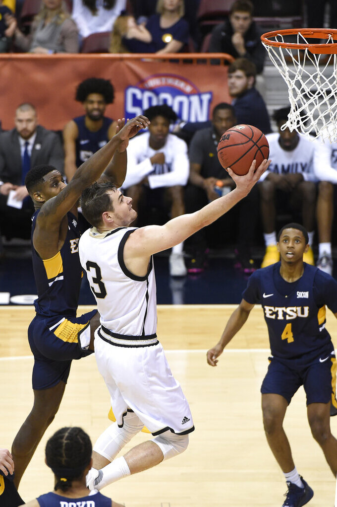 Wofford guard Fletcher Magee (3) drives the ball to the basket against East Tennessee State guard Bo Hodges (3) as East Tennessee State guard Daivien Williamson (4) looks on in the first half of a semi-final NCAA college basketball game in the Southern Conference tournament championship, Sunday, March 10, 2019, in Asheville, N.C. (AP Photo/Kathy Kmonicek)