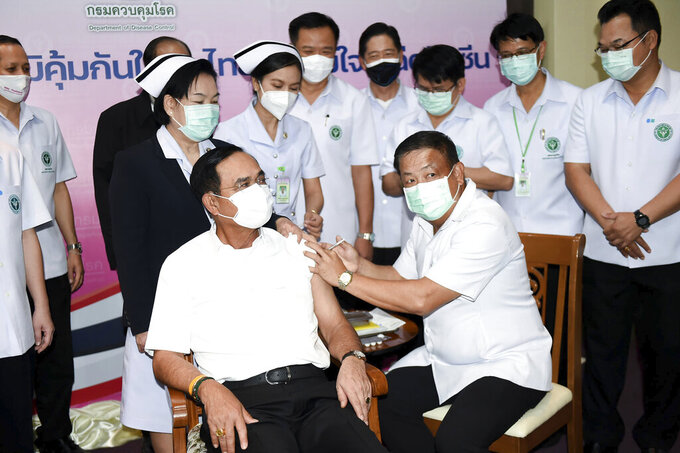 A health worker administers the second dose of the AstraZeneca COVID-19 vaccine to Thailand's Prime Minister Prayuth Chan-ocha, center left, at Bamrasnaradura Infectious Diseases Institute in Bangkok, Thailand, Monday, May 24, 2021. (Government Spokesman Office via AP)