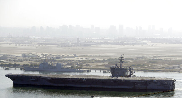 The USS Theodore Roosevelt aircraft carrier makes its way into San Diego Bay Thursday, July 9, 2020, seen from San Diego. The carrier returned home to San Diego Thursday, led by a new captain who came aboard after the previous commander was fired and the Navy secretary resigned over the handling of a massive COVID-19 outbreak on board. (AP Photo/Gregory Bull)