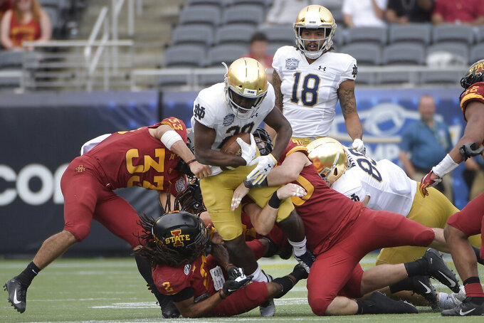 FILE - Notre Dame running back C'Bo Flemister (20) is tackled by Iowa State defensive back Braxton Lewis (33), defensive back Datrone Young (2) and linebacker Jared Gescheidler (40) after rushing for yardage during the second half of the Camping World Bowl NCAA college football game Saturday, Dec. 28, 2019, in Orlando, Fla. With all the success Notre Dame has enjoyed its last three seasons, amassing a 33-6 record under coach Brian Kelly, it has been the inability to run the football successfully in big games that has curtailed the championship hopes of the Fighting Irish. (AP Photo/Phelan M. Ebenhack, File)