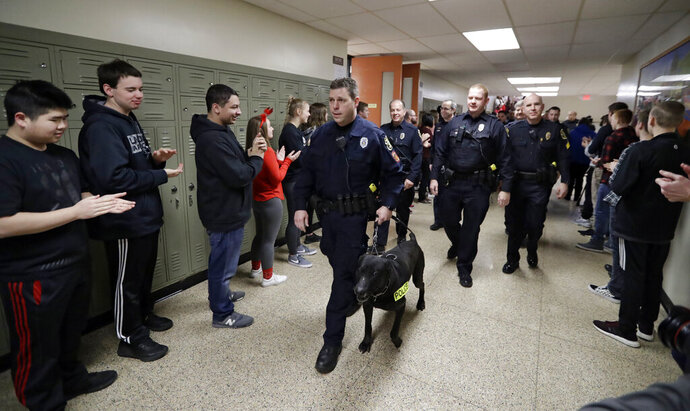 Boardman High School students clap as Officer Daryn Tallman and his K-9, Sumo, walk the halls after a lockdown drill, Thursday, Feb. 14, 2019, in Boardman, Ohio. Some students around the country marked the anniversary of the school massacre in Parkland, Florida, with moments of silence Thursday or somber vigils while others sought to find threads of positivity in the fabric of tragedy. (AP Photo/Tony Dejak)