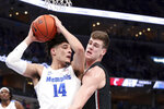 Memphis' forward Isaiah Maurice (14) grabs a rebound as Cincinnati's center Chris Vogt (33) defends in the first half of an NCAA college basketball game Thursday, Jan. 16, 2020, in Memphis, Tenn. (AP Photo/Karen Pulfer Focht)