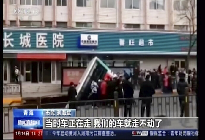 In this image made from CCTV video, a bus plunges into a sinkhole in the center of a downtown street, Monday, Feb. 13, 2020, in Xining, Qinghai province, China. Authorities say the bus plunged through a collapsed section of road in northwestern China, killing a number of people. (CCTV via AP)