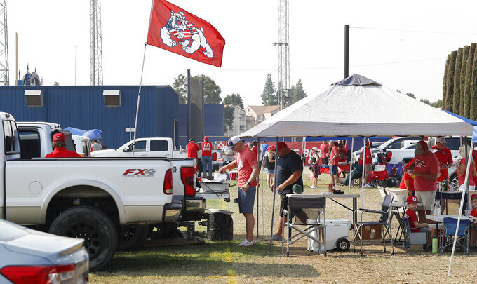 Anthony Dejager cooks on the grill at his tailgate party before the Connecticut at Fresno State NCAA college football game in Fresno, Calif., Saturday, Aug. 28, 2021. Colleges across the country are cautiously optimistic that pregame tailgating atmospheres around campus will remain close to normal even as they monitor how things have changed since the emergence of the delta variant. (AP Photo/Gary Kazanjian)