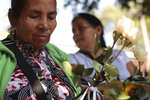 Juana Bonilla, 66, holds white roses as she waits with her relatives to receive six small coffins containing the remains of their family members who were killed in a 1982 massacre, in San Salvador, El Salvador, Thursday, Jan. 23, 2020. The remains of six adults and children from one family were handed over to surviving relatives Thursday, 38 years after the El Calabozo massacre, in which government soldiers are accused of killing more than 200 people.(AP Photo/Salvador Melendez)