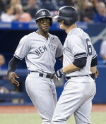 New York Yankees' DJ LeMahieu, right, crosses home plate next to Cameron Maybin after hitting a three-run home run in the sixth inning against the Toronto Blue Jays in a baseball game Wednesday, June 5, 2019, in Toronto. (Fred Thornhill/The Canadian Press via AP)