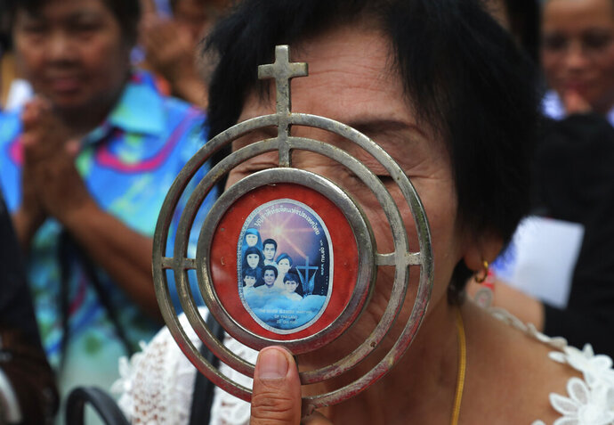 In this Saturday, Oct. 19, 2019, photo, a Catholic devotee kisses a sacramental with an image of the seven martyrs at cemetery during the 30th anniversary of the beatification of seven martyrs at Songkhon in Mukdahan province, northeastern of Thailand. In 1940, seven villagers here were executed for refusing to abandon their Catholic faith, which Thai nationalists had equated with loyalty to France, whose colonial army in neighboring Indochina had fought Thailand in a brief border war. The seven were beatified in 1989 by Pope John Paul II, the first step to being named a saint.(AP Photo/Sakchai Lalit)