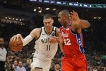 Milwaukee Bucks' Brook Lopez drives past Philadelphia 76ers' Al Horford during the first half of an NBA basketball game Saturday, Feb. 22, 2020, in Milwaukee. (AP Photo/Morry Gash)
