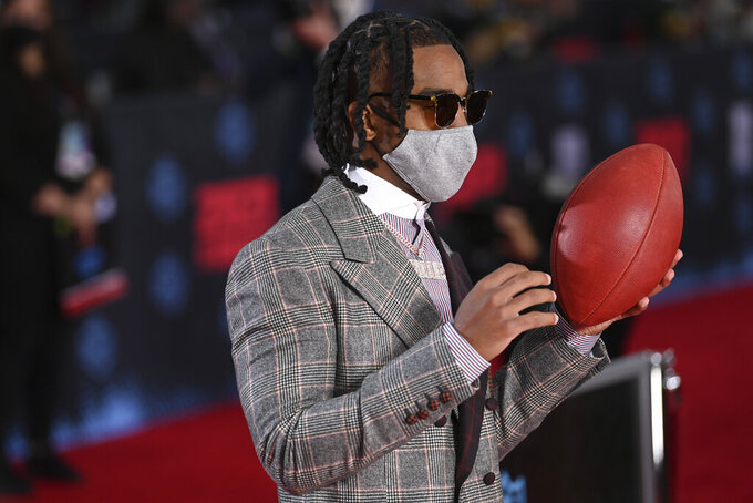 Alabama wide receiver Jaylen Waddle holds a football as he appears on the red carpet at the Rock & Roll Hall of Fame before the NFL football draft, Thursday, April 29, 2021, in Cleveland. (AP Photo/David Dermer, Pool)