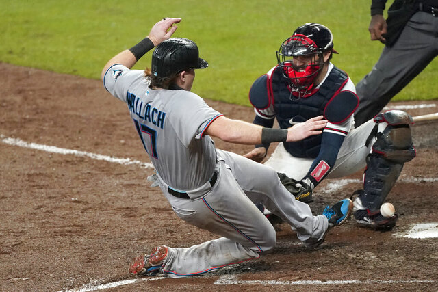 Miami Marlins' Chad Wallach (17) scores on a Jon Berti double as the ball gets away from Atlanta Braves catcher Travis d'Arnaud during the sixth inning of a baseball game Thursday, Sept. 24, 2020, in Atlanta. (AP Photo/John Bazemore)