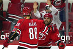 Carolina Hurricanes left wing Jordan Martinook (48) is congratulated by center Martin Necas (88) after his goal during the second period of an NHL hockey game against the Dallas Stars in Raleigh, N.C., Sunday, April 4, 2021. (AP Photo/Gerry Broome)