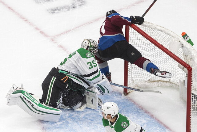 Colorado Avalanche's Tyson Jost (17) crashes into Dallas Stars' goalie Anton Khudobin (35) during the first period of an NHL hockey Stanley Cup playoff game in Edmonton, Alberta, Friday, Sept. 4, 2020. (Jason Franson/The Canadian Press via AP)