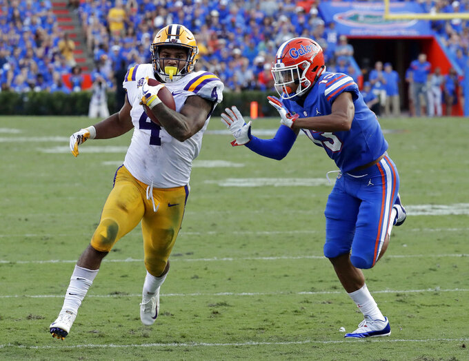 LSU running back Nick Brossette (4) runs for 46 yards before he is run out of bounds by Florida safety Donovan Stiner, right, during the second half of an NCAA college football game Saturday, Oct. 6, 2018, in Gainesville, Fla. (AP Photo/John Raoux)
