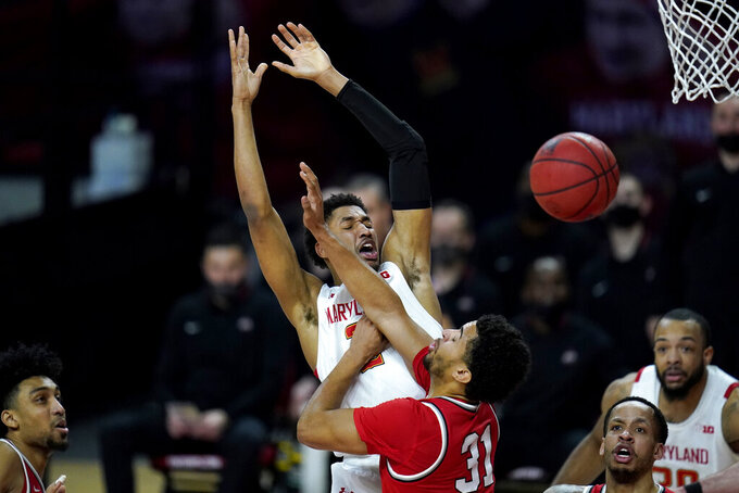 Maryland guard Aaron Wiggins, left, is fouled by Ohio State forward Seth Towns during the first half of an NCAA college basketball game, Monday, Feb. 8, 2021, in College Park, Md. (AP Photo/Julio Cortez)