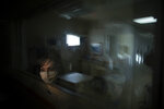 """In this photo created with an in-camera multiple exposure, registered nurse Cathy Cullen, part of the first group of nurses who had been treating coronavirus patients in an intensive care unit, stands for a photo in the empty COVID-19 ICU at Providence Mission Hospital in Mission Viejo, Calif., Tuesday, April 6, 2021. Cullen sometimes tears up when thinking about what she and the other nurses endured. """"The birth of my children and marriage aside, being a part of this team, this endeavor, and this pandemic is by far the greatest, worst, most rewarding, most painful thing I have ever done in my life,"""" she says. (AP Photo/Jae C. Hong)"""